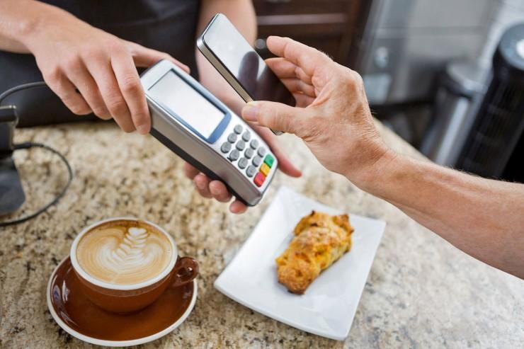 So wird das Smartphone zur elektronischen Geldbörse. Bei Beträgen unter 25 Euro muss nur noch das Smartphone vor das Lesegerät gehalten werden - fertig. Foto: djd/Volkswagen Financial Services /Tyler Olson - Fotolia.com